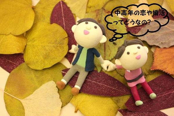 落ち葉の上で空を仰いでるカップルの粘土の写真