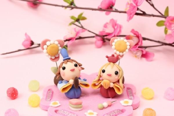 花見をしている粘土で出来た男の子と女の子の画像