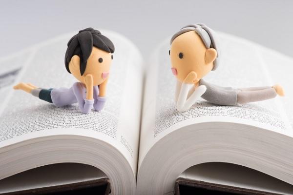 本の上で話し合っている男女の粘土画像